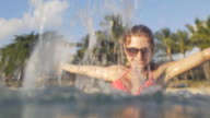 Woman relaxing in ocean with tropical beach in background, splashing video