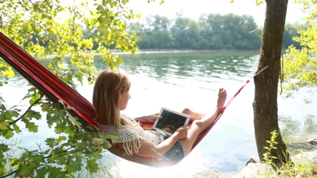 Woman relaxing on a hammock with digital tablet video