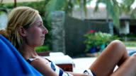Woman relaxing on a lounge chair by the pool video