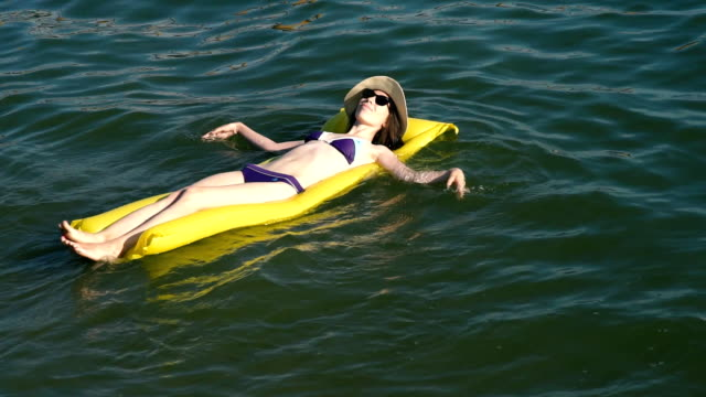 Woman relaxing on inflatable mattress at the beach video
