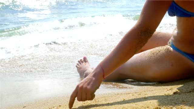 Woman relaxing on the beach, waves splashing in her body, legs only video
