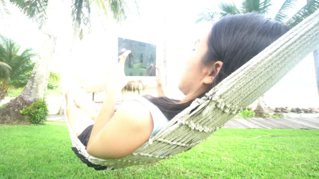 Woman relaxing with degital tablet in beach hammock video