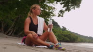 Woman resting and drinking water after run. video