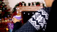 Woman resting with cup of hot drink near fireplace video