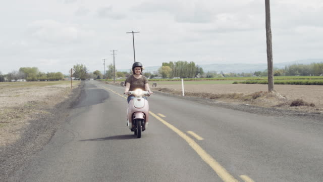 Woman riding down a country road on a scooter video