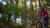 Woman riding mountain bike through forest in sunshine video