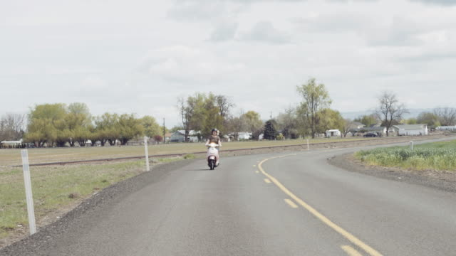 Woman riding scooter down country road on a sunny day video
