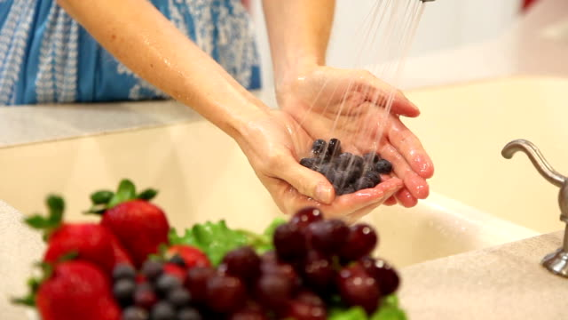 Woman rinses blueberry fruits in home kitchen sink. video