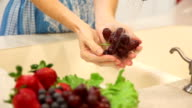 Woman rinses red grapes in home kitchen sink. video