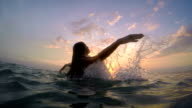 Woman rises from sea at sunset video