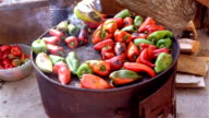 Woman roasting red and green peppers video