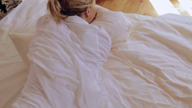 Woman rolling in bed with pillow video