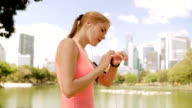 Woman runner jogging in park. Fit female sport fitness training. Using smartwatch checking cellphone video