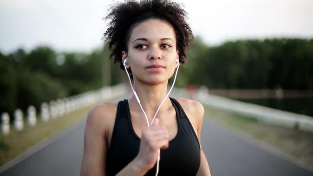 Woman runner running at sunrise. Full face video
