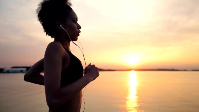 Woman runner running at sunrise video