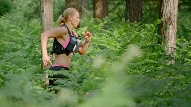 SLO MO DS Woman running a marathon through forest video