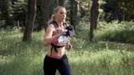 SLO MO DS Woman running a trail marathon amongst the forest trees video