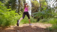 SLO MO DS Woman running across a forest clearing in sunshine video