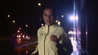SLO MO Woman running along a city street at night video