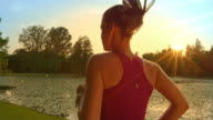 SLO MO TS Woman running along lake at sunset video
