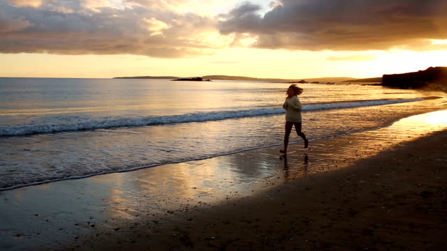 Woman running along the water at sunset video