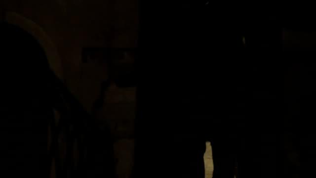 Woman running in dark alleyway at night video