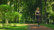 Woman running in park. Fitness woman jogging outdoor. Runner training in park video