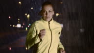 SLO MO TS Woman running in city at night in rain video