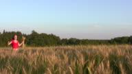 woman running in wheat field video