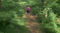 AERIAL Woman running on forest path in sunshine video