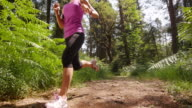 SLO MO TS Woman running on a forest trail in sunshine video