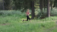 SLO MO DS Woman running on forest trail in sunshine video