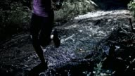 SLO MO DS Woman running on a muddy forest trail at night video
