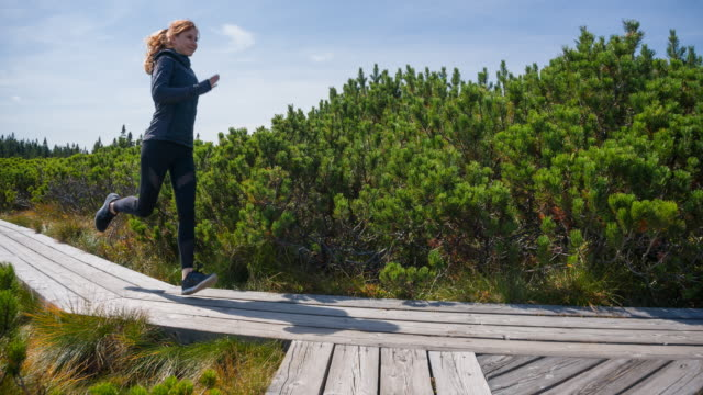Woman running on a wooden pathway among pine bushes video
