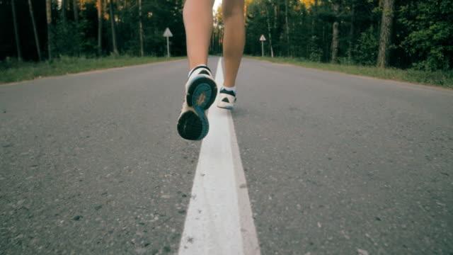 Woman running on asphalt road, slow motion video