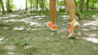 Woman running on dirt path, view of feet and running shoes video