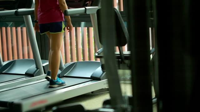 woman running on treadmills in modern sport gym video