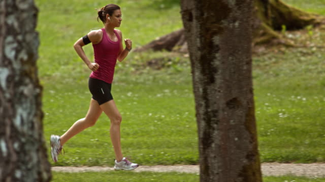 SLO MO TS Woman running through a park listening to music video