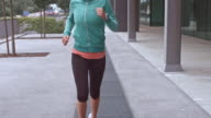 SLO MO TS Woman running through city in the morning video