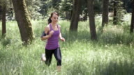 SLO MO DS Woman running through forest listening to music video