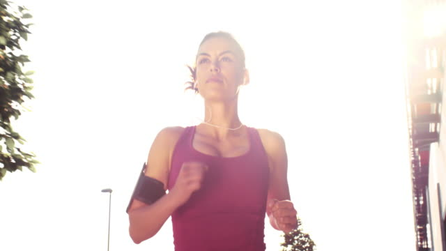 SLO MO TS Woman running through the city on a hot day video