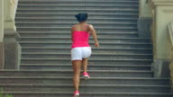 Woman running up stairs in slow motion. Running woman on staircase video