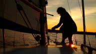 Woman sailor working on sailboat at sunset, hobby, active rest video