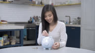 Woman saving coins putting them in her piggy bank video