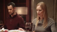 Woman saying grace before Thanksgiving meal with family at table video