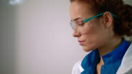Woman scientist in safety glasses. Close up of female scientist face video