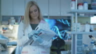 Woman scientist is walking with documents in a laboratory where colleagues are working. video