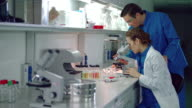 Woman scientist looking microscope. Lab assistant bring notepad to science woman video