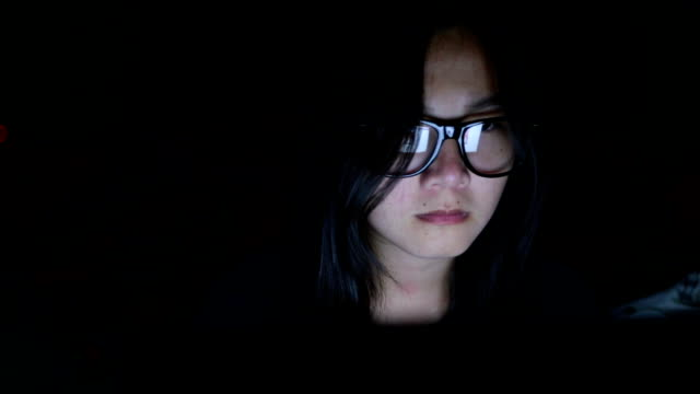 Woman search internet on laptop in the dark video
