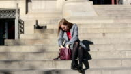 Woman searching something in her hand bag sitting on stairs of building video